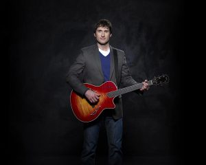 Dave Carroll in a jacket with a guitar